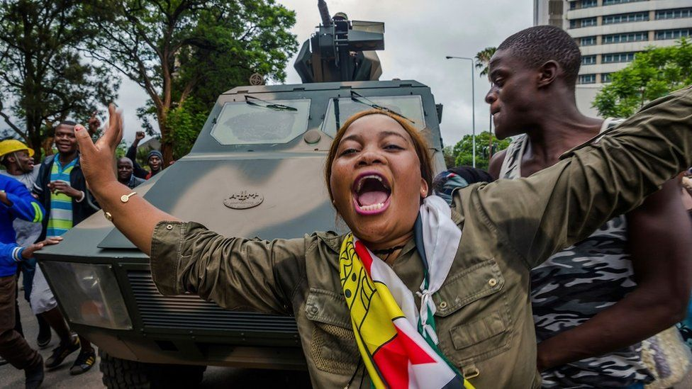 woman singing and dancing in front of army tank