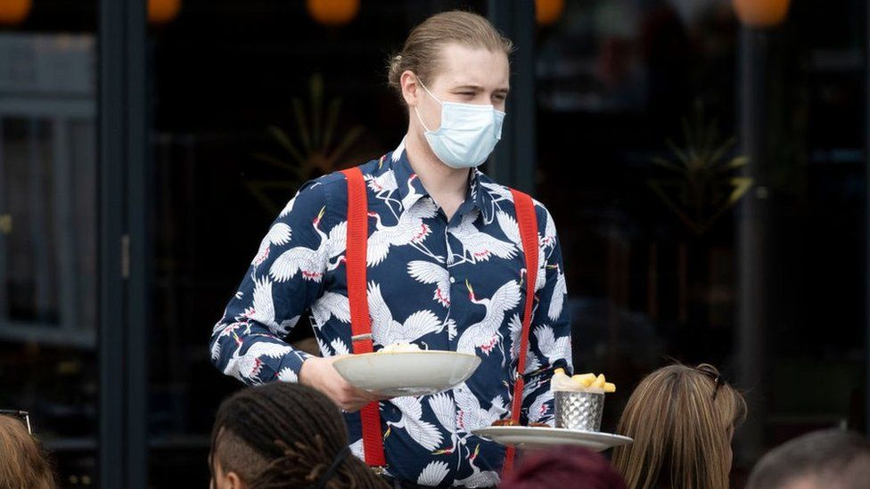 Waiter wearing a face mask.