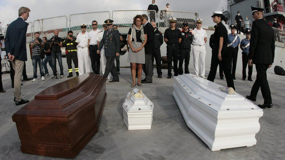 Officials pay their respect in front of the coffins of refugees arrived from Lampedusa on October 15, 2013 in Porto Empedocle near Agrigento in Sicily