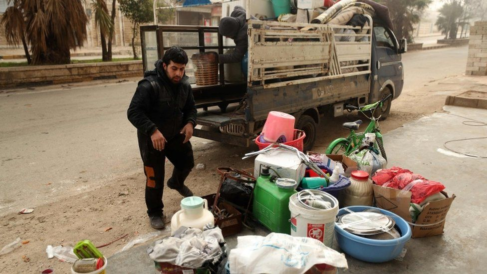 A man loads a truck as Syrian government forces bear down on Maaret Al-Numan