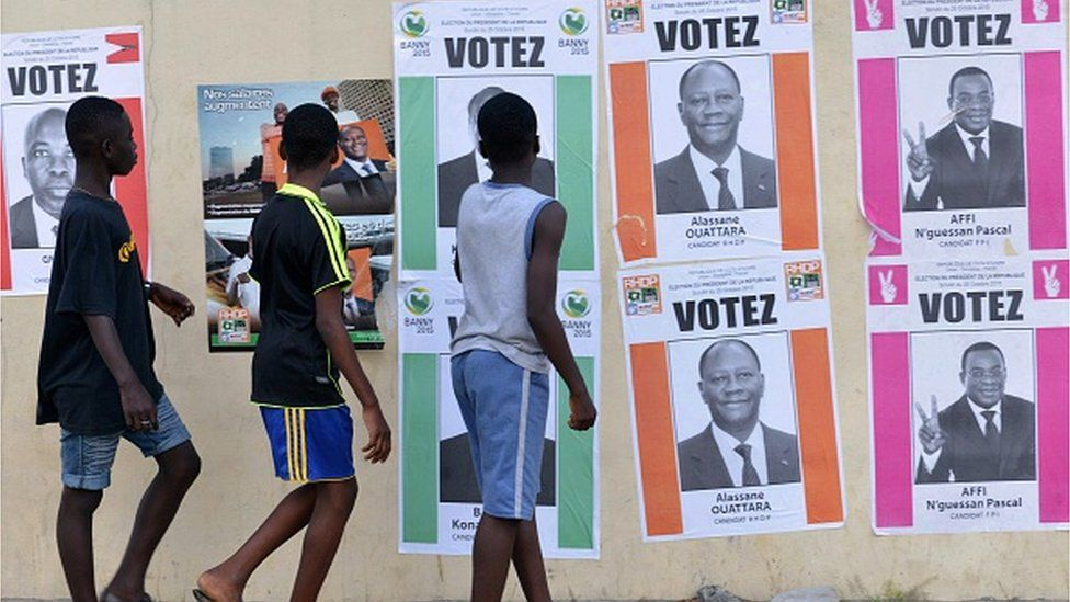 Boys walk past Ivory Coast's presidential election candidates campaign posters on October 14, 2015 in Cocody Abidjan.