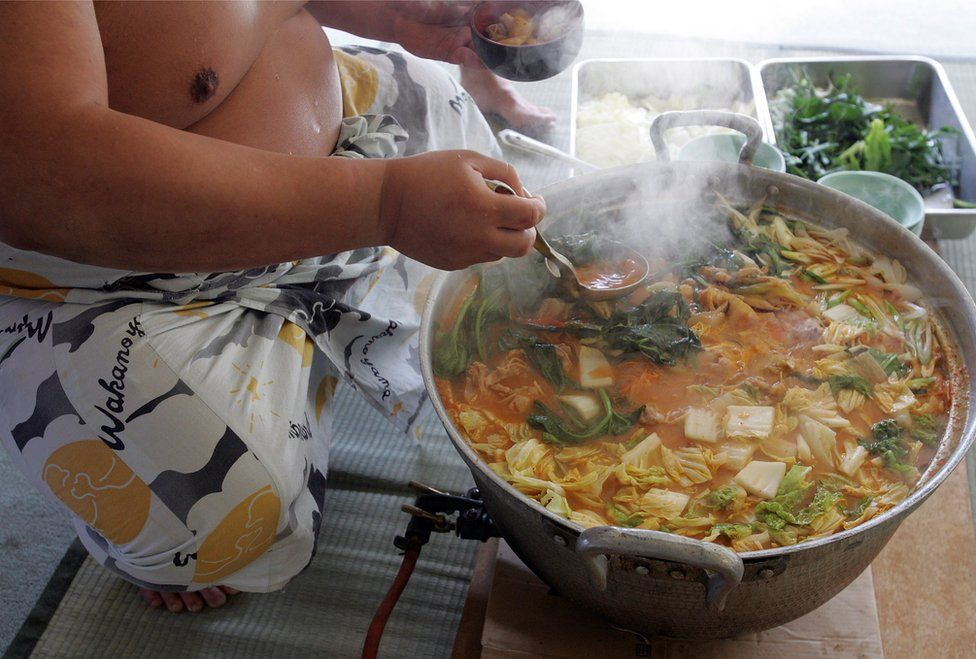 A sumo wrestler dishes up 'chanko-nabe' during a 'Sumo Diet Campaign' event at Musashigawa Sumo Stable on March 1, 2007 in Osaka, Japan.