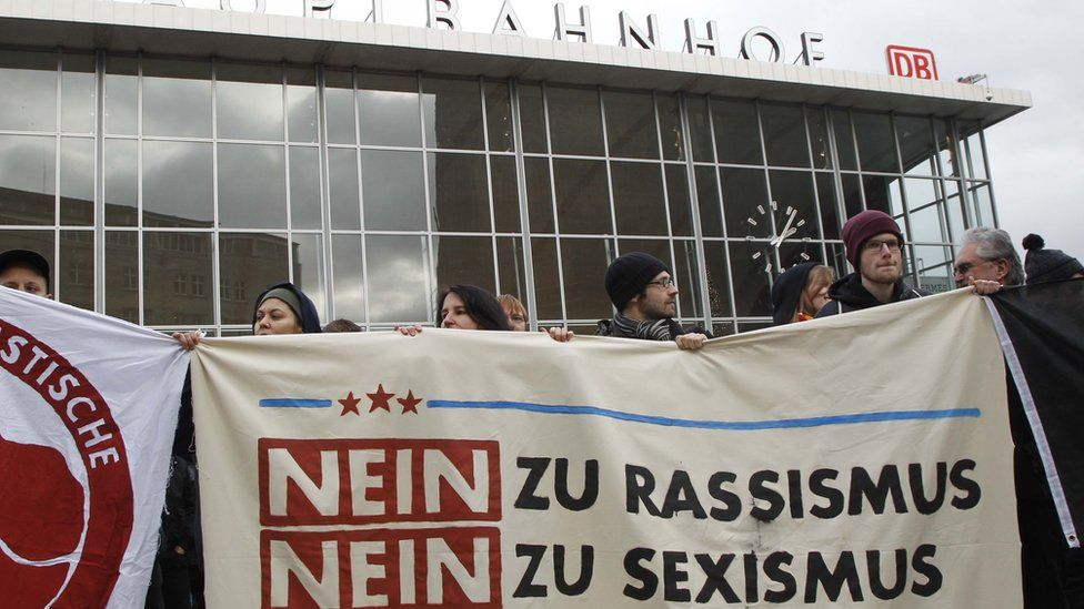 """People protest in front of the main station in Cologne, Germany, on Wednesday, Jan. 6, 2016. The poster reads: """"No to Racism, No to Sexism""""."""
