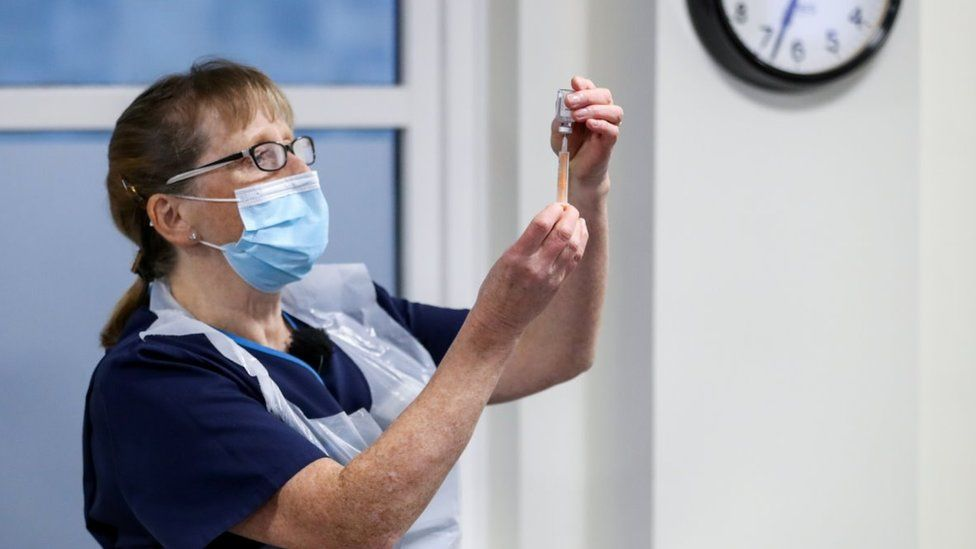 A healthcare worker holds a vial of AstraZeneca coronavirus disease (COVID-19) vaccine and a syringe at the Pentland Medical Practice, in Currie, Scotland, Britain January 7, 2021.