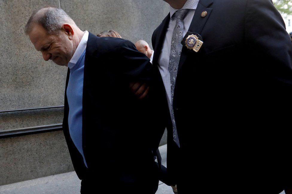 Harvey Weinstein is escorted by police
