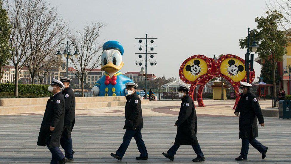 Staff workers wear protective masks in Shanghai Disneyland Park.