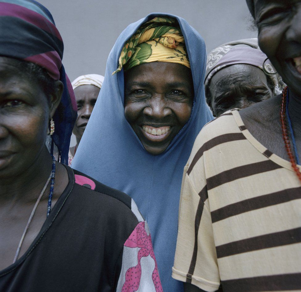 A woman smiles out from a group.