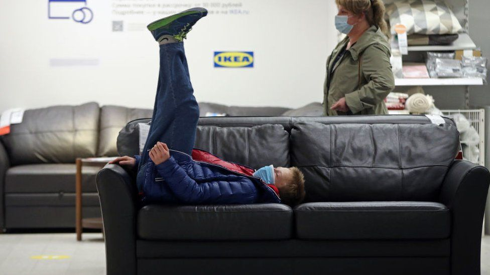 Ikea shopper on his back on sofa