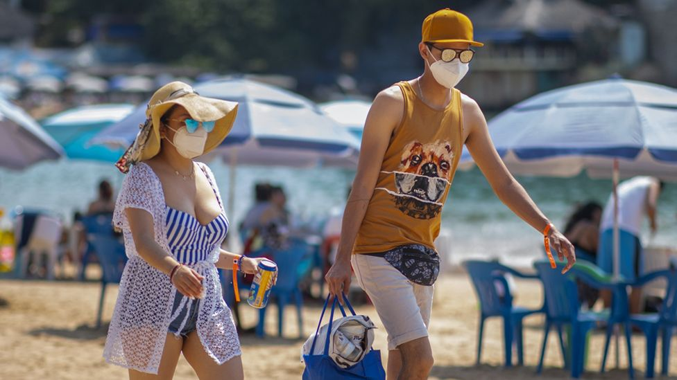 Tourists wearing a mask walk along Caleta beach on March 19 2021 in Acapulco, Mexico