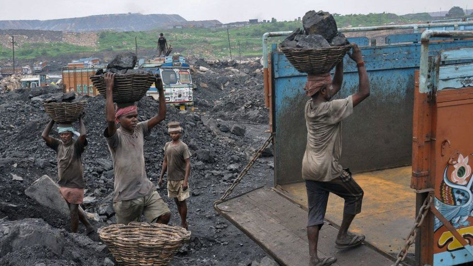 This photo taken on December 7, 2017 shows Indian labourers loading coal onto trucks at an open mine in Dhanbad in the eastern Indian state of Jharkhand.