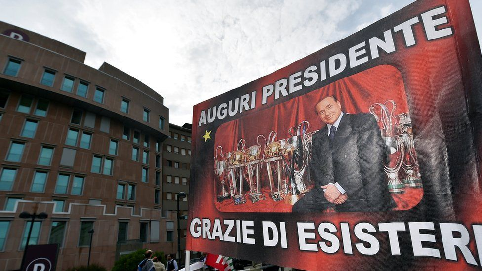 """All the best, president - thanks for being there"", a banner reads outside the hospital in Milan where Mr Berlusconi underwent the operation"