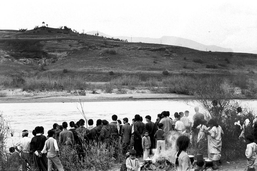 Kurdish people wait on the Iraq side of the Khabur River