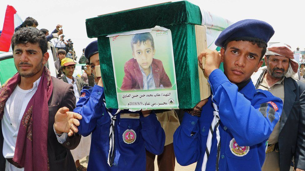 Scouts carry the coffin of a boy during the funerals on 13 August 2018 of people killed in a Saudi-led coalition air strike in Saada, Yemen.