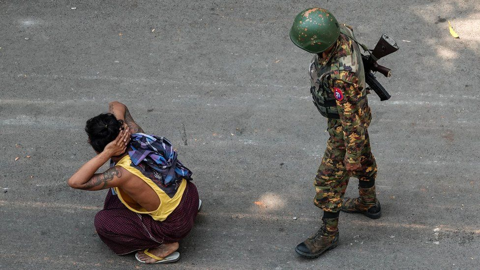 Pria duduk di lantai di sebelah tentara