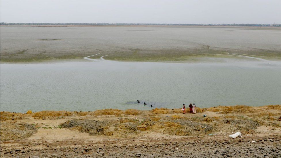 Women stand by the dried-up puzhal reservoir on the outskirts of Chennai, capital of the southern Indian state of Tamil Nadu, Wednesday, June 20, 2019.