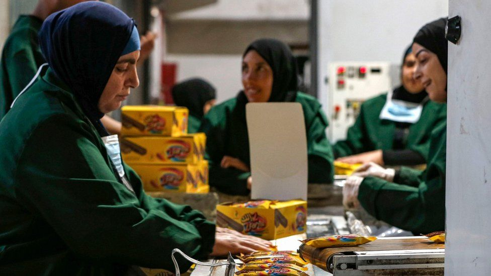 Palestinian women work at a factory in the West Bank city of Ramallah (17 June 2019)