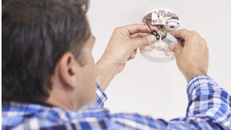A man changes a smoke alarm's battery