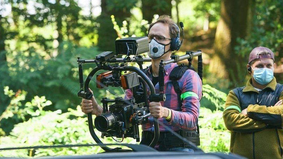 A camera operator wearing a mask holding a camera