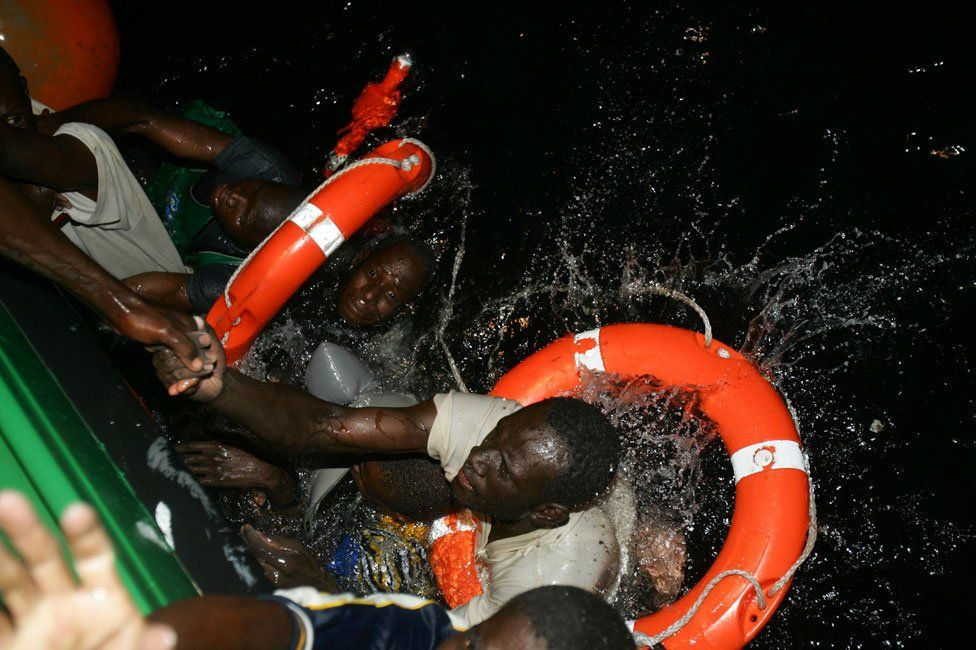 Isa and Ibrahim, both from Mali, being pulled from the water