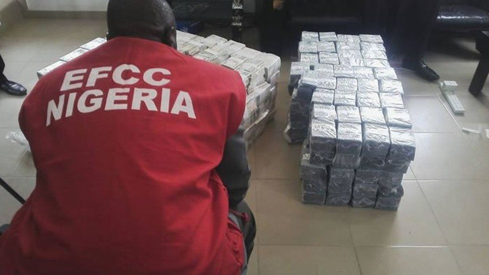 An official of the Nigeria's economic and financial crime commission squats before bundles the seized cash