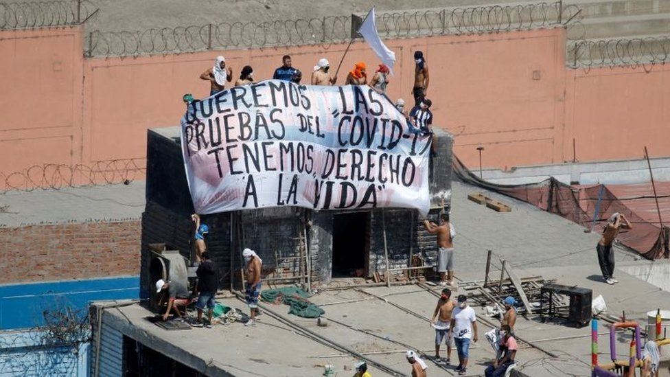 """Inmates at the Lurigancho jail hold a banner reading: """"We want Covid-19 tests, we have the right to life"""""""