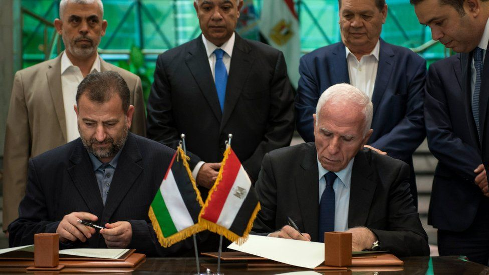 Palestinian member of Fatah Central Committee, Azam al-Ahmed (right), and Hamas deputy head of the politburo Saleh al-Aruri sign an agreement between the two Palestinian factions in Cairo, Egypt, 12 October 2017