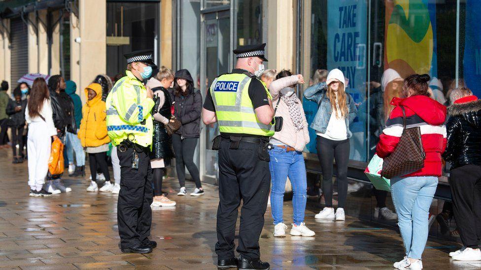 Police officers patrol as customers queue outside the Primark store on Princes Street in Edinburgh on June 29