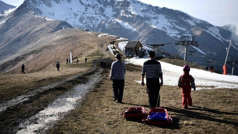 People pull a sled on the top of a ski slope near Luchon, in French Pyrenees