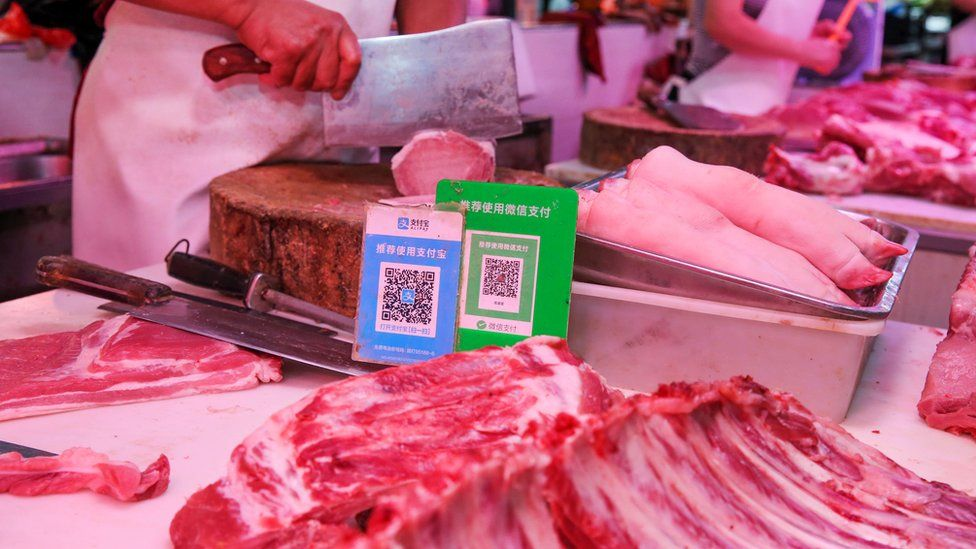Alipay and wechat QR codes for online payment are displayed at a meat stall at a market in Nantong in China's eastern Jiangsu province on September 10, 2018.