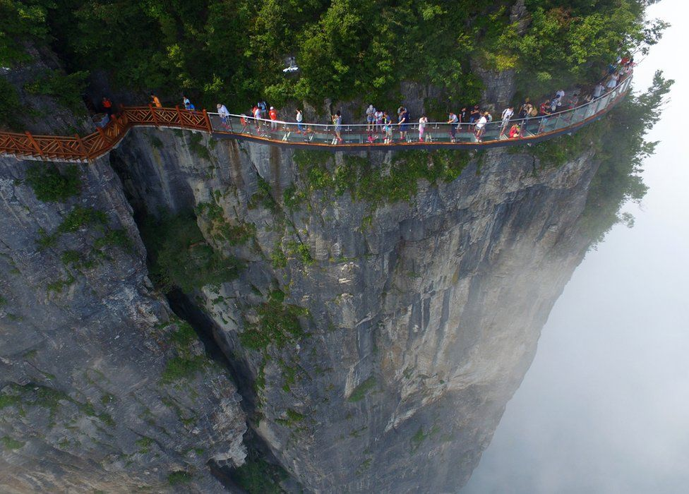 People walk around a glass walkway in Tianmen Mountain in Zhangjiajie National Forest Park, Hunan, China (1 August 2016)