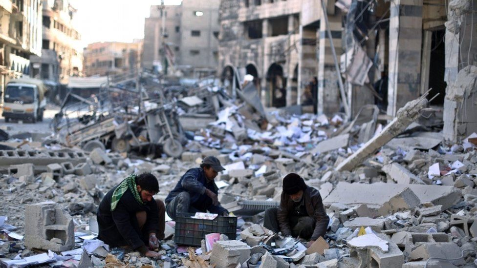 Syrians pick amongst the debris around the bombed out remains of a local council building hit in an airstrike carried out by forces allied with the al-Assad regime on opposition held Douma, outskirts of Damascus, Syria, 30 December 2015