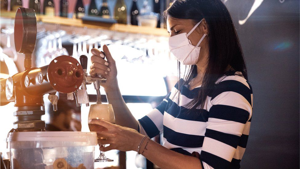 A woman pulling a pint wearing a mask