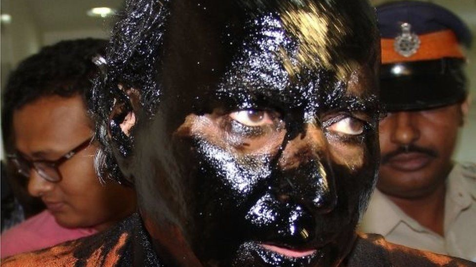 Indian activist Sudheendra Kulkarni, whose face was blackened by ink in an alleged attack, is escorted by policemen ahead of a press conference in Mumbai on October 12, 2015.