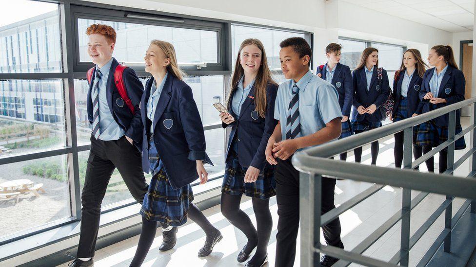 Teenagers walking in school corridor