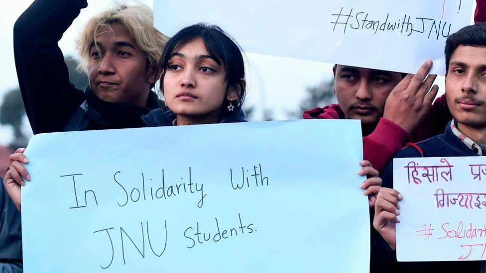 Students from Jawaharlal Nehru University (JNU) hold placards as they express their solidarity following an attack there