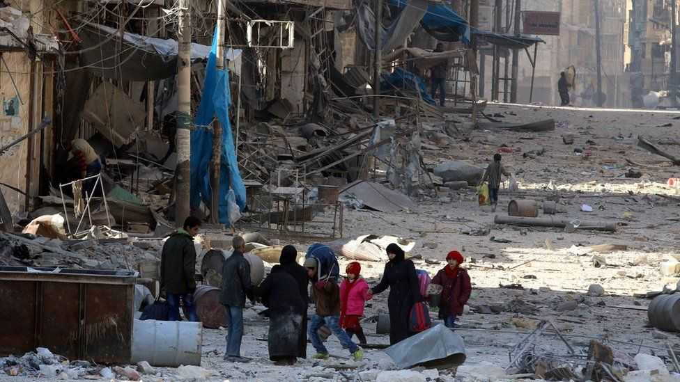 Syrians walk over rubble of damaged buildings, while carrying their belongings, as they flee clashes between government forces and rebels in Tariq al-Bab and al-Sakhour neighbourhoods of eastern Aleppo towards other rebel held besieged areas of Aleppo