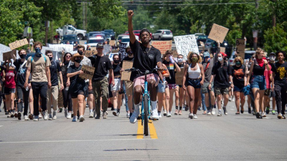 Demonstrators raise signs in the air during as they march in protest for the 15th straight day over the death of George Floyd