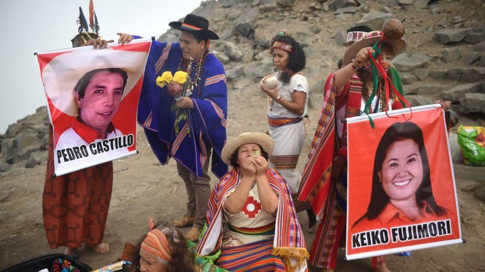 Shamans hold posters of presidential candidates Pedro Castillo (L) and Keiko Fujimori as they perform a ritual to predict the winner of the upcoming Peruvian run-off election, at San Cristobal Hill in Lima on 26 May 2021.