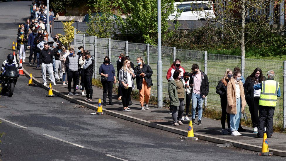 People queue outside a mobile Covid vaccination centre in Bolton