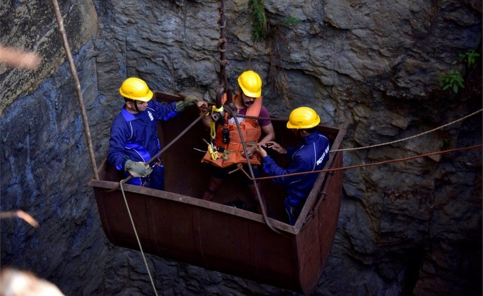 Divers use a pulley to enter the stricken coal mine on 29 December, 2018