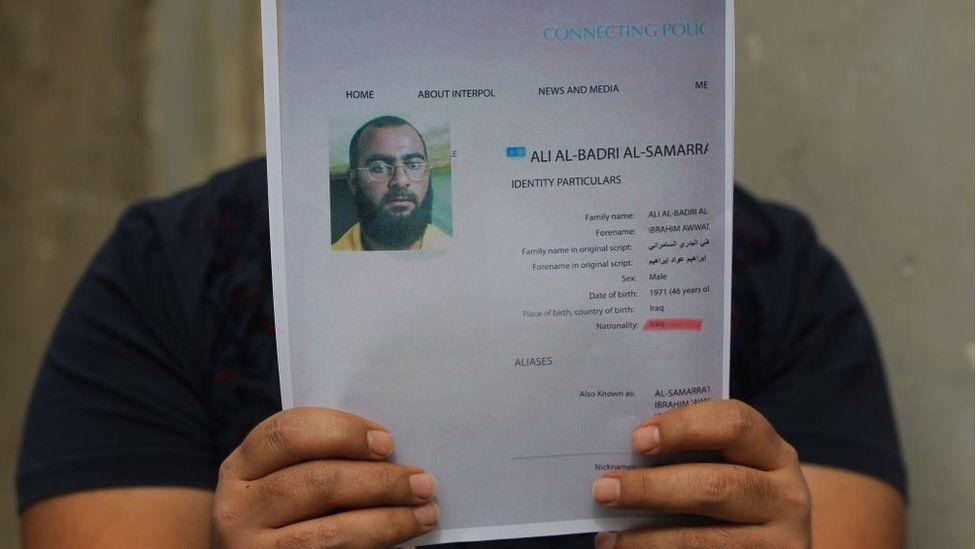 An Iraqi man holds printed profiles of Abu Bakr al-Baghdadi released by Iraqi authorities on 6 February 2018