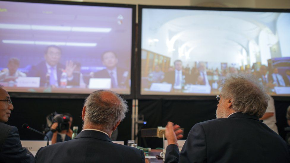Austrian scientists sit in front of two screens during record-breaking video call with Chinese scientists