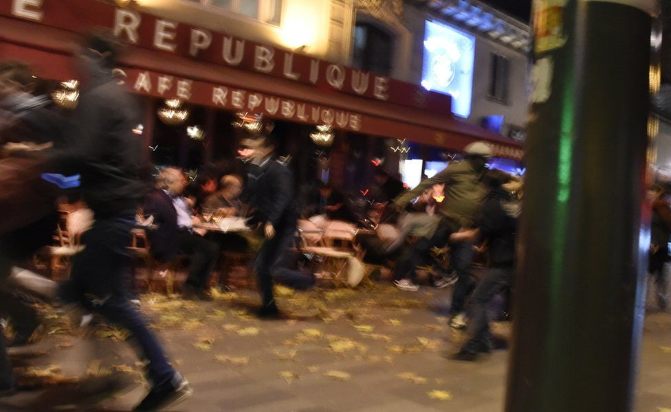 People sitting outside a cafe as people run past after a shooting in Paris