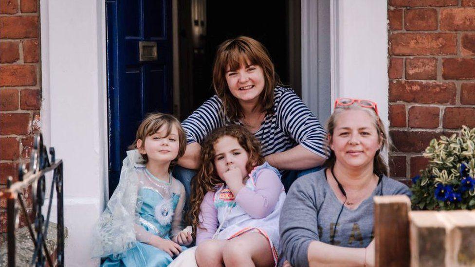 A family sitting on their doorstep