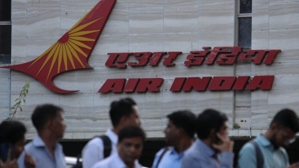 People walk past an Air India logo outside its building in Mumbai, India on 28 January 2020