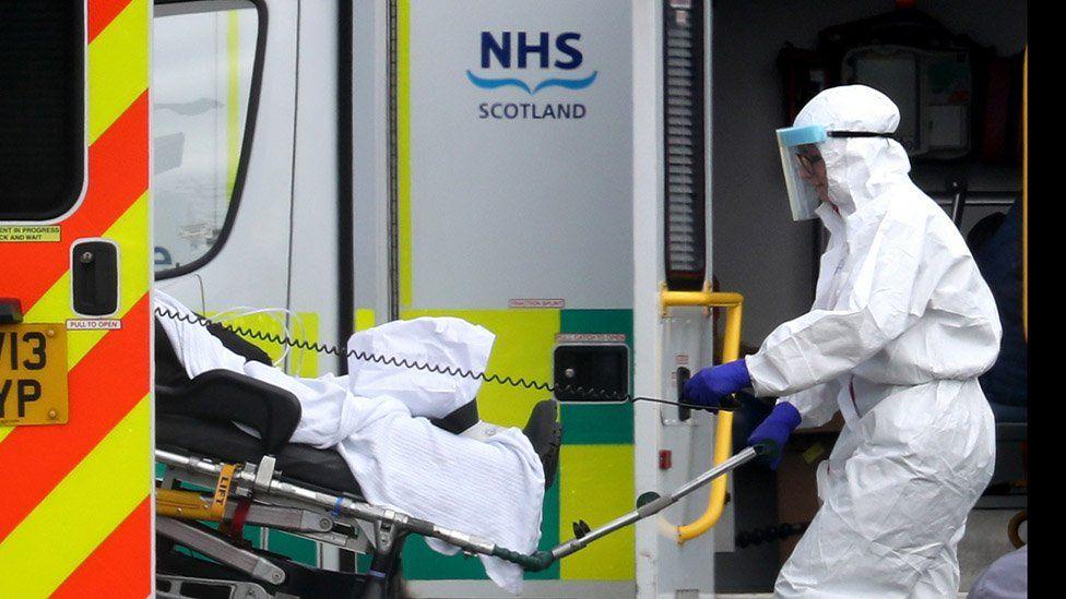 A hospital worker by an ambulance