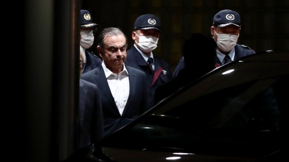 Carlos Ghosn is escorted as he walks out of the Tokyo Detention House following his release on bail in Tokyo in April 2019