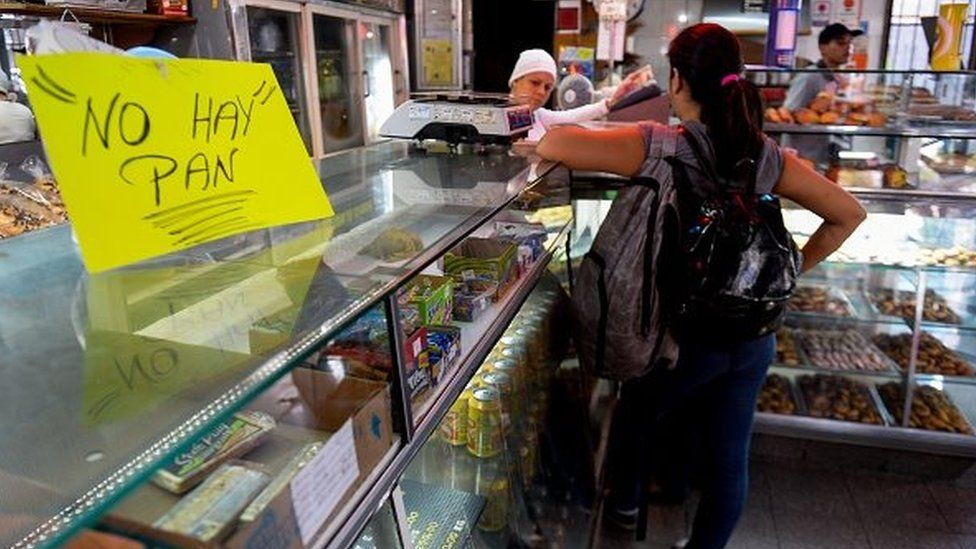 """A woman waits at a bakery displaying a sign reading """"No Bread"""", in Caracas on 25 February 2016"""