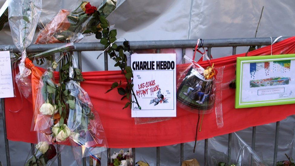 Memorial outside Bataclan venue with flowers and a banner about Charlie Hebdo