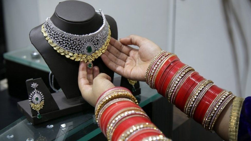 An Indian woman looks at gold jewellery at a shop on 09 November 2016.